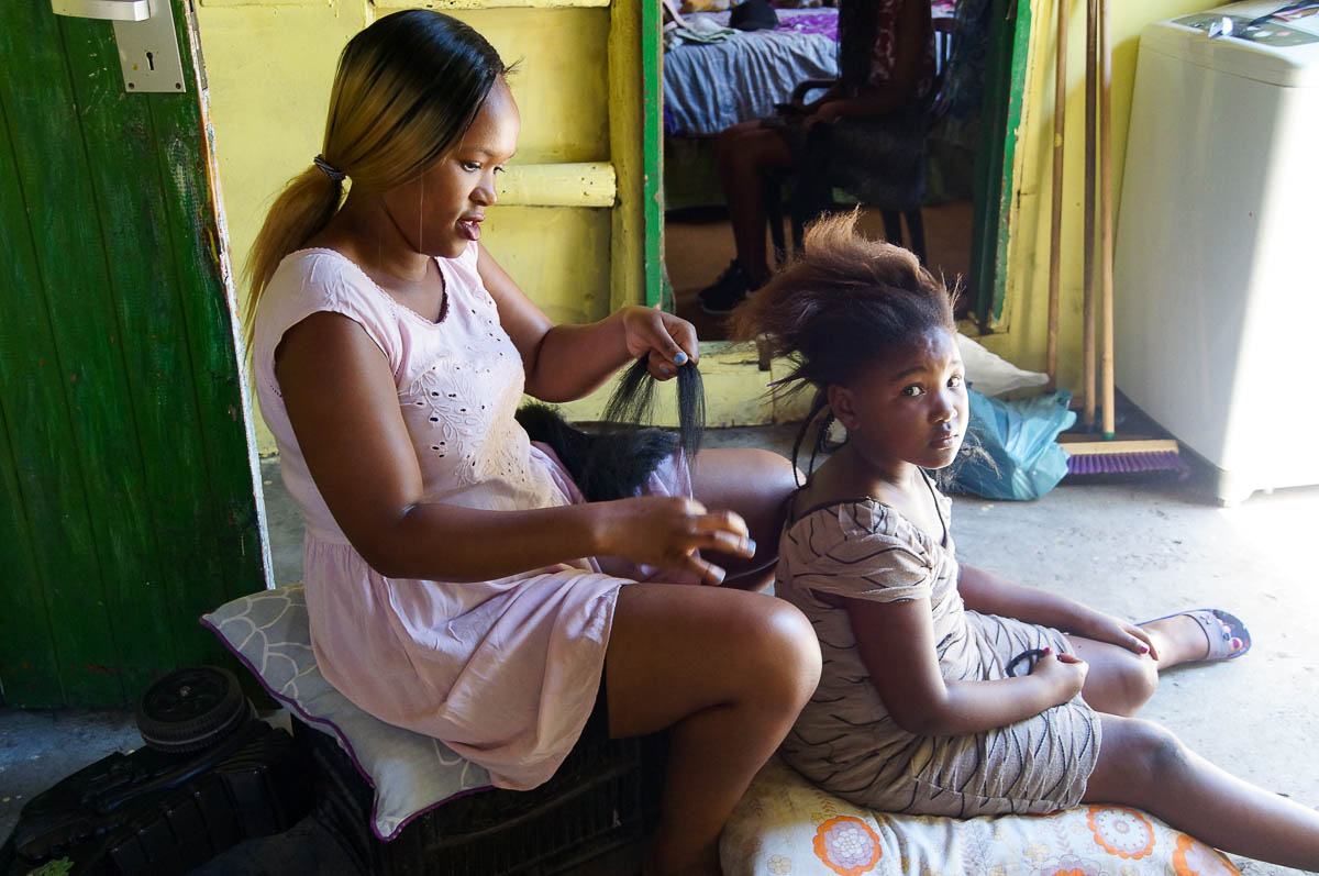 mother and daughter doing rasta hair in twonship