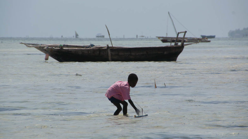boy playing with little boat in front of wooden boats at Jambiani beach