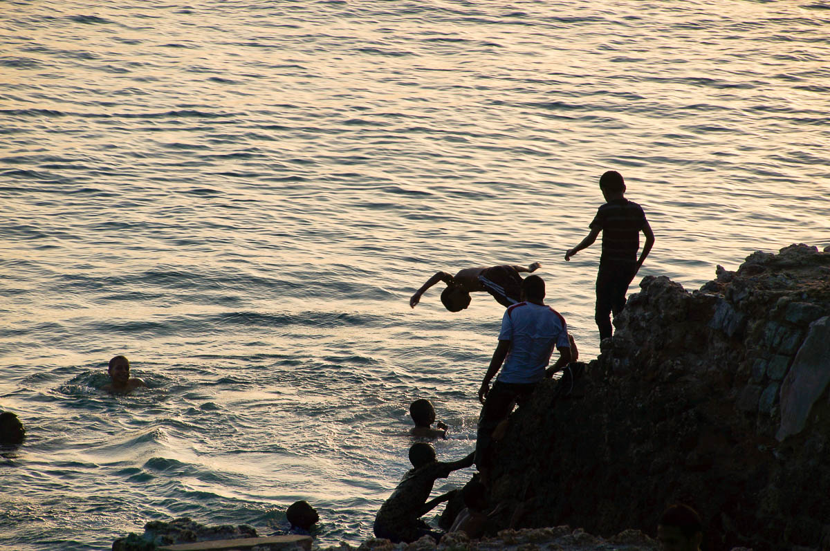 kids jumping into the water at sunset in Stonetown