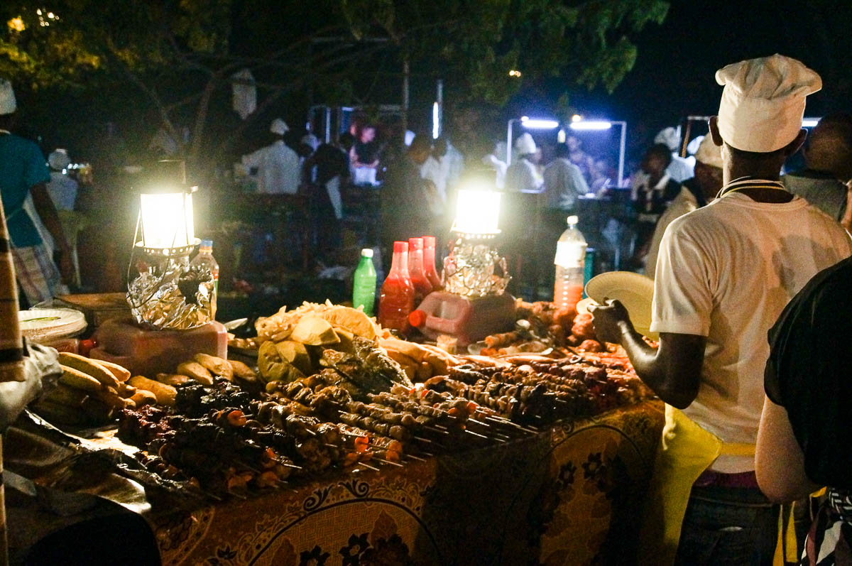man selling food at Stonetown night market