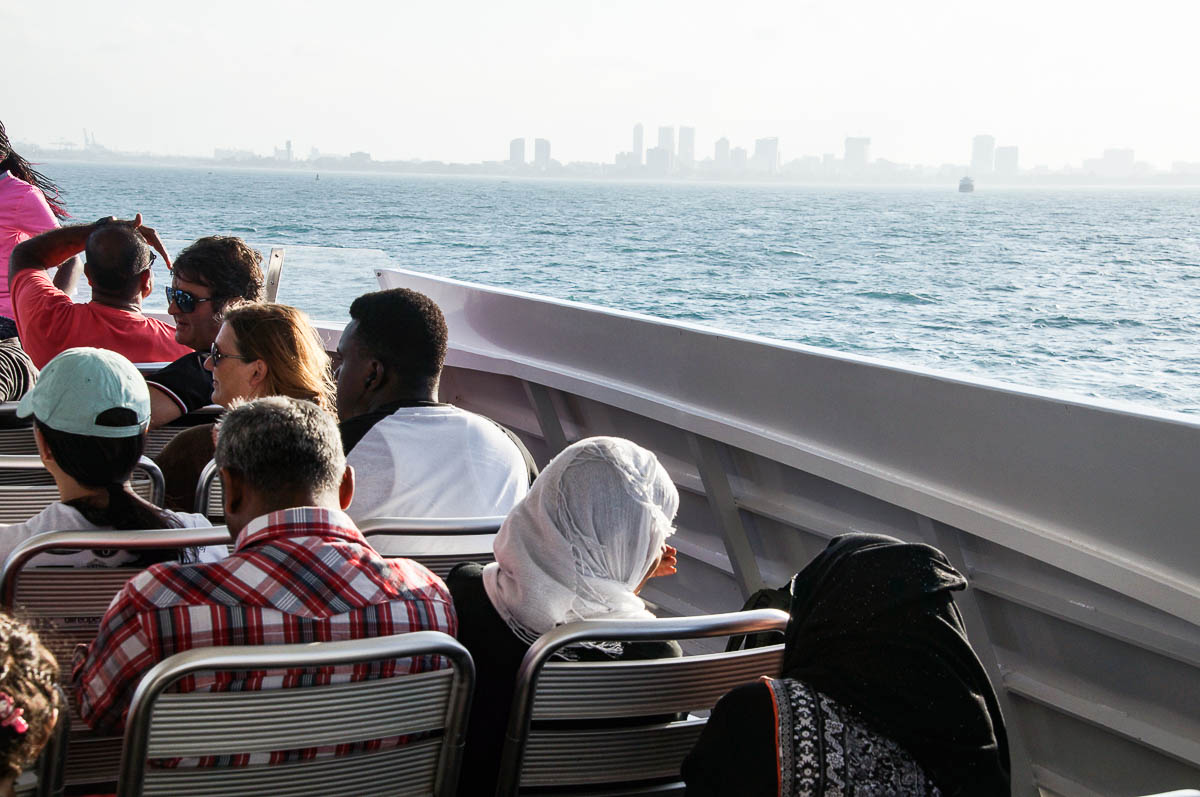 people on ferry with skyline of Daressalam in background