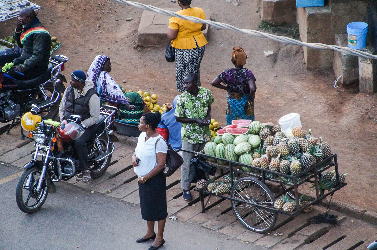 woman on street in Moshi with fruit sellers